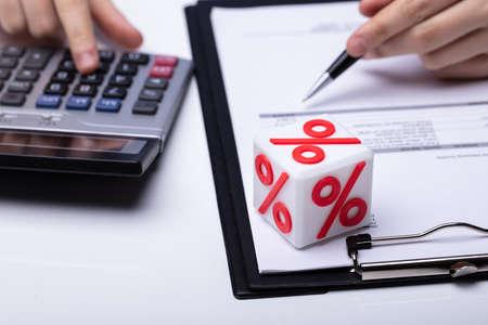 Nahaufnahme des weißen Blocks mit Prozentsymbol, während Unternehmer Rechnung über weißen Schreibtisch berechnen Standard-Bild