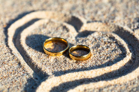 An Overhead View Of Golden Wedding Rings Inside The Heart Shape On Sand At Beach Stockfoto