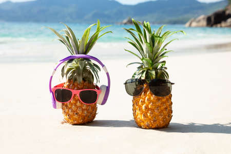 Close-up Of Pineapple With Headphone And Sunglasses On Sand At Beach