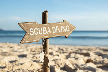 Close-up Of Scuba Diving Directional Wooden Sign On Beach