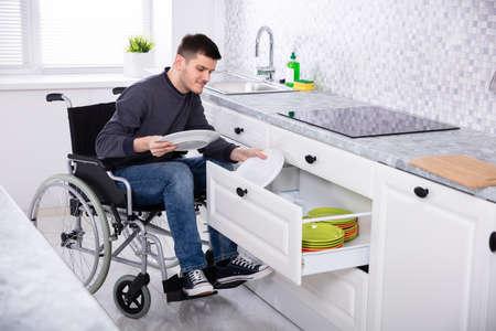Jonge gelukkig gehandicapte man zittend op rolstoel platen in lade schikken