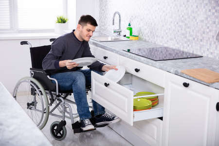 Young Happy Disabled Man Sitting On Wheelchair Arranging Plates In Drawer