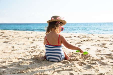 Rear View Of Toddler Girl Wearing Hat Playing On Sand With Toys At Beach