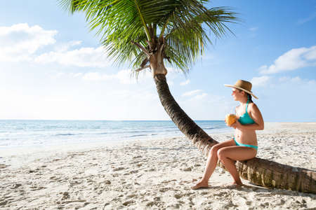Young Woman In Bikini Sitting On Palm Tree Trunk Drinking The Coconut Water At Beach