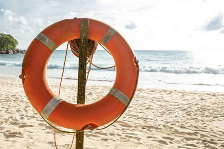 Close-up Of An Orange Lifebuoy In Front Of Sea At Beach Stockfoto