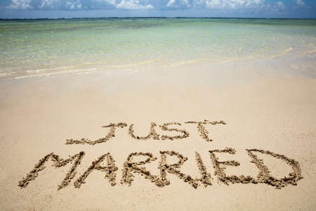 Just Married Written Text On Sand Near The Idyllic Sea At Beach