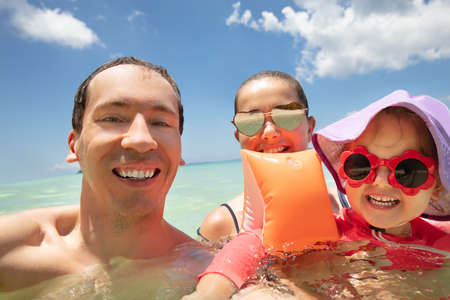 Close-up Of A Smiling Young Family With Their Daughter Swimming In The Sea 写真素材