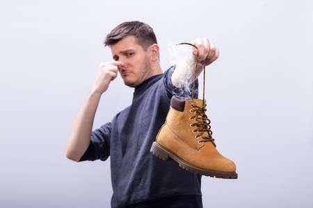 Close-up di un uomo che copre il naso mentre si tiene una scarpa puzzolente su sfondo bianco