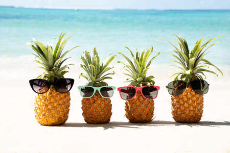 Family  Of Pineapples With Different Color Sunglasses Near Sea On Beach