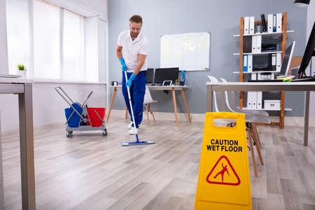 Conserje masculino con trapeador limpieza piso de la oficina moderna