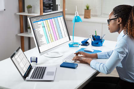 Vista lateral de la mano de la empresaria analizando datos en la computadora sobre el escritorio Foto de archivo