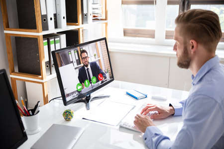 Side view of businessman video conferencing with coworker on desktop PC at office desk