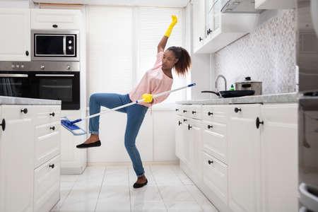 Nahaufnahme einer jungen afrikanischen Frau beim Wischen des Bodens in der Küche ausrutschen