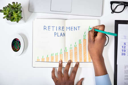 Elevated View Of A Human's Hand Drawing Retirement Plan Growth Concept On Notebook