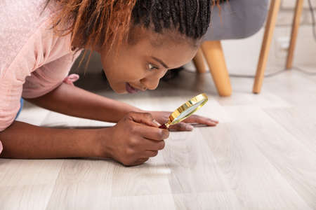 Side View Of A Young Woman Looking At Hardwood Floor Through Magnifying Glass