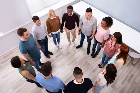 Group Of Multi-ethnic People Standing In Circle Holding Each Other Hands