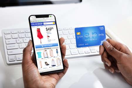 Een vrouw die online winkelt met mobiele telefoon en creditcard