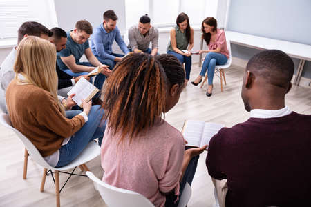 Group Of Young Multi-ethnic People Reading Holy Bible Together Banque d'images