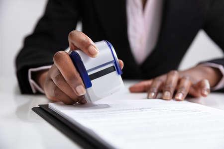 Close-up de la empresaria poniendo sello en los documentos en la oficina. Foto de archivo
