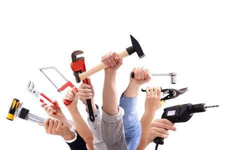 Close-up Of People's Hand Holding Carpentry Tools Against White Background