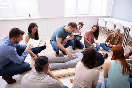 Männlicher Spezialist, der während des Trainings eine Massage am Mann durchführt