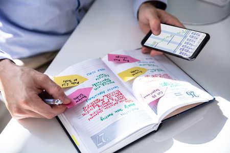 Close-up de manos de persona con teléfono móvil y lista de trabajo en diario