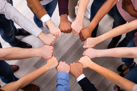 An Overhead View Of Multi-ethnic People's Hand Joining Their Fist To Form Circle