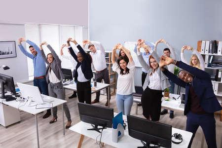 Groep lachende multi-etnische zakenmensen doen rekoefeningen op de werkplek Stockfoto