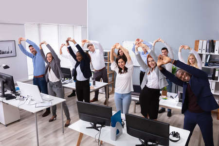Gruppo di imprenditori multietnici sorridenti che fanno esercizio di stretching sul posto di lavoro Archivio Fotografico
