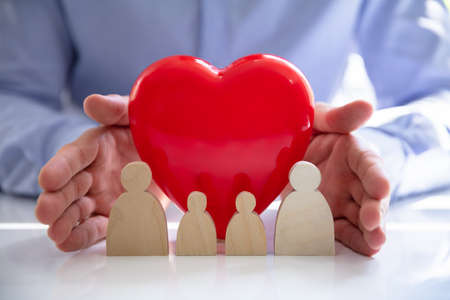 Person's hand protecting red heart with family figures