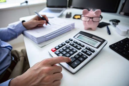 Close-up Of A Businessperson's Hand Calculating Bill With Calculator In Office