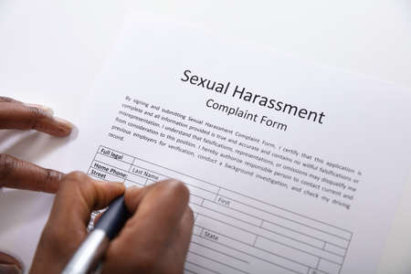 An Elevated View Of Human Hand Filling Sexual Harassment Complaint Form With Pen Фото со стока