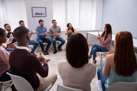 Gruppe junger Menschen lernen taube Geste Zeichen von Frau auf Stuhl sitzend