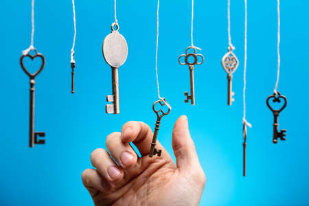 Close-up Of Person's Hand Choosing A Hanging Key Amongst Other Ones Banque d'images