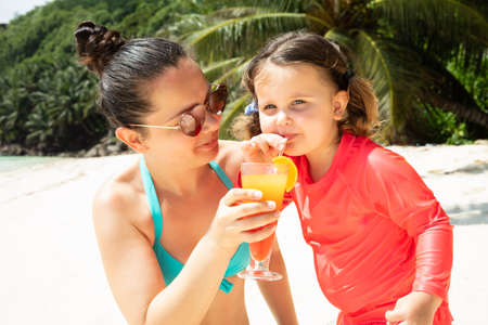 Portrait Of A Daughter Drinking The Juice From Glass Hold By Her Mother At Beach