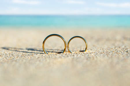 Golden And Shiny Wedding Rings On Sand At Beach