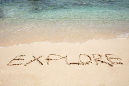 Close-up Of Explore Text Written On Sand Near The Seaside At Beach