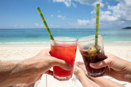 Close-up Of Couple's Hand Clinking The Glasses Of Juice With Drinking Straw On Beach