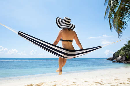 Rear View Of A Woman In Bikini Sitting On Hammock Looking Over Sea At Beach Imagens