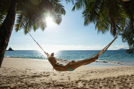 Woman Lying On The Hammock Between The Palm Trees In Front Of Sea At Beach