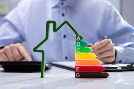House With Energy Efficiency Rate In Front Of Businesspeople Working On Documents