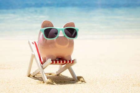 Nahaufnahme von rosa Sparschwein mit türkisfarbenen Sonnenbrillen auf Miniatur-Liegestuhl auf Sand am Strand? Standard-Bild