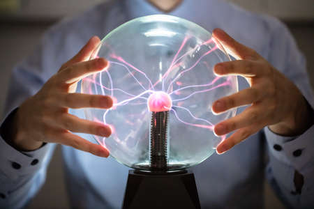 Close-up Of Fortune Teller Holding Hand Over The Glowing Crystal Ball Stock Photo