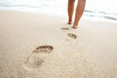 Untere Partie der Frau zu Fuß auf Sand in Richtung Meer am Strand an einem sonnigen Tag Standard-Bild
