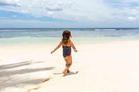 Little Girl In Bikini Walking On The Idyllic Anse Baleine Beach, Mahe Island, Seychelles Фото со стока