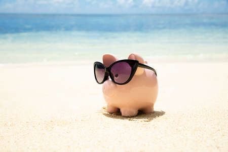 Pink Piggybank Wearing Black Sunglasses On The Sand At Beach