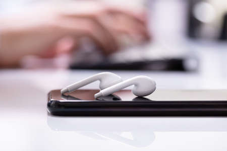 Close-up Of Wireless Earphone On Mobile Phone Over White Desk Reklamní fotografie