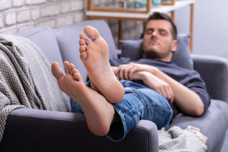 Close-up Of Man Relaxing On Sofa With His Legs Crossed In Home Stockfoto