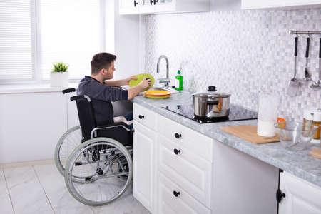 Uomo disabile seduto su sedia a rotelle lavare e pulire i piatti in cucina