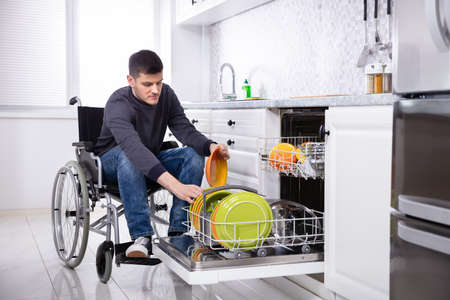 Young Handicapped Man Sitting On Wheelchair Arranging Plates In Dishwasher Stock Photo